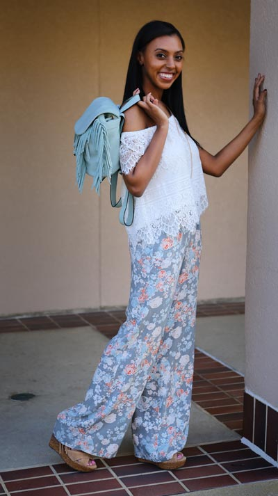 Andrea is wearing Cupcakes and Cashmere white lace off the shoulder top & BCBGeneration floral wide leg pant with Jessica Simpson wedges and Melie Bianco fringe backpack purse.